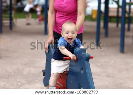 Happy child is playing on wooden horse at playground