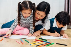 Happy child kid boy and girl kindergarten drawing on peper teacher education with beautiful mother at interior room home