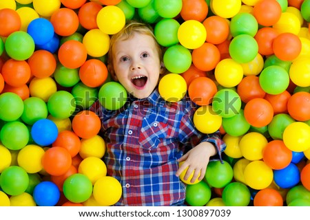 Happy child, kid boy playing, having fun on playground with colorful plastic balls in pool. Game center for family weekend, holiday party with kids, games area room. Entertainment center with toys.