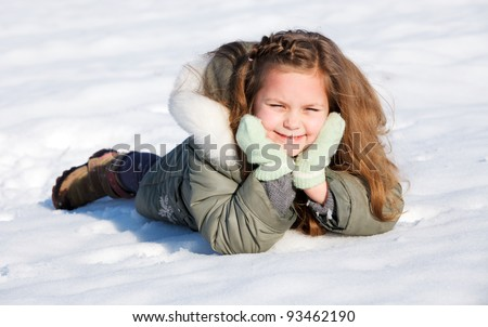 Happy child laying down in the snow