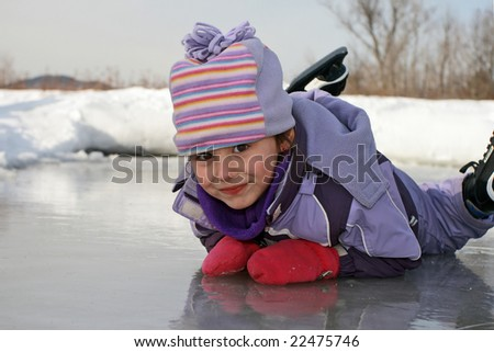 Happy child laying on skating rink ice surface during winter.