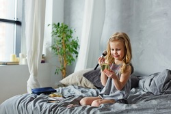 Happy child. Little cute girl doing makeup on the bed in the bedroom . The girl is laughing with makeup brushes in her hands