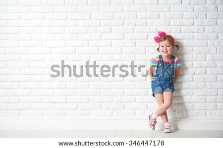 Happy child little girl laughing at a blank empty brick wall #346447178