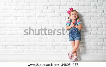 Happy child little girl laughing at a blank empty brick wall #348054257