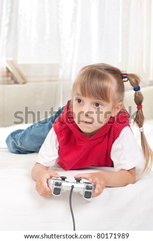Happy child - little girl playing a video game