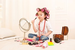 Happy child. Little pretty girl makes a make-up on a bed in the bedroom . Girl laughing with curlers on her head , and brushes for makeup in the hands