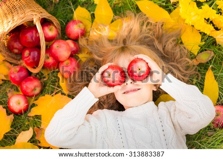 Happy child lying on fall leaves. Funny kid outdoors in autumn park