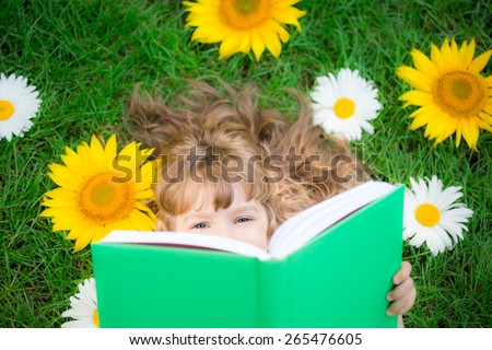 Happy child lying on green grass. Funny kid reading the book in spring park
