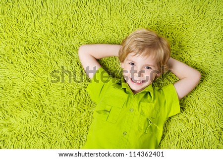Happy child lying on the green carpet background. Boy smiling and looking at camera - stock photo