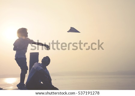 happy child makes fly his paper airplane