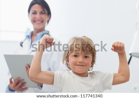Happy child next to a doctor in hospital ward