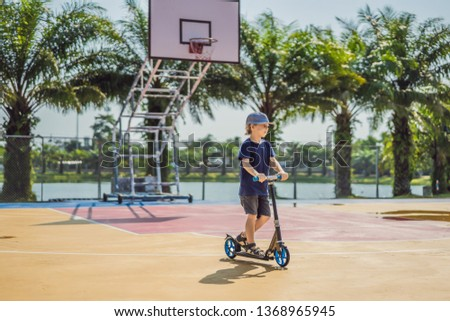 Happy child on kick scooter in on the basketball court. Kids learn to skate roller board. Little boy skating on sunny summer day. Outdoor activity for children on safe residential street. Active sport #1368965945