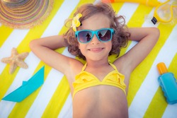 Happy child on the beach. Kid having fun outdoors. Summer vacation concept. Top view portrait