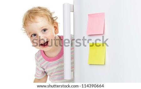 happy child or boy hiding behind fridge door