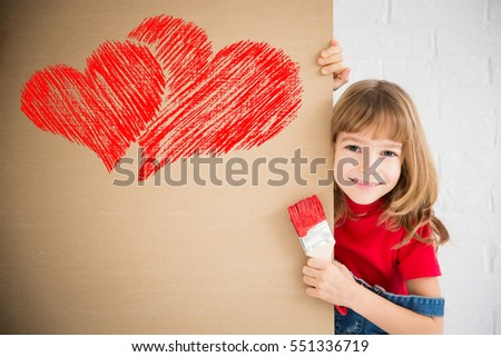 Happy child painting big red heart on the wall. Funny girl playing at home. Valentines day card. Renovation and design concept #551336719