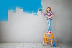 Happy child painting the wall with blue color. Kid having fun at home. Spring renovation concept