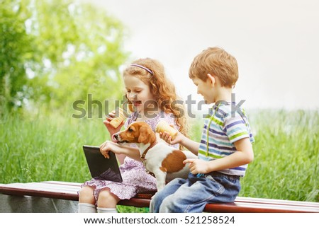 Happy child playing and having fun with her puppy. Girl playing in the tablet PC and eating ice cream in summer park. Leisure, friendship or family concept.