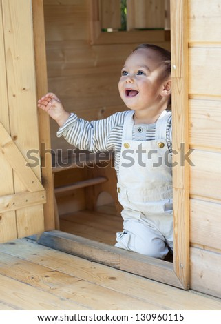 Happy child playing in a wooden playhouse or a small garden shed, kneeling at the door looking up.