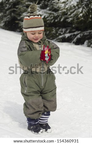 Happy child playing in fresh snow in winter.