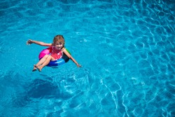 Happy child playing in swimming pool. Summer vacation concept. Top view portrait