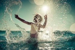 Happy child playing in the sea. Kid having fun outdoors. Summer vacation and healthy lifestyle concept. Toned image