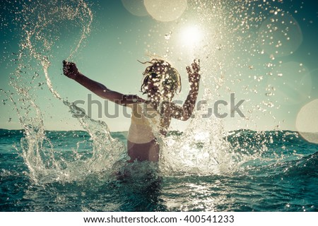 Happy child playing in the sea. Kid having fun outdoors. Summer vacation and healthy lifestyle concept. Toned image #400541233