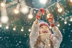 Happy child playing on a snowy winter walk. Little girl enjoying the holidays. Portrait kid on dark background.