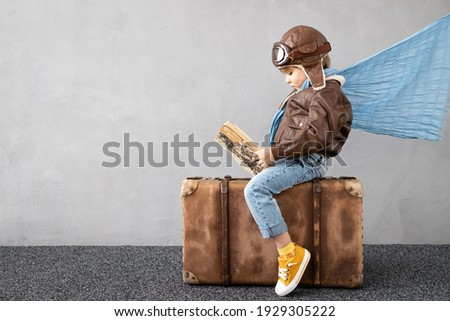 Happy child playing outdoor. Smiling kid dreaming about summer vacation and travel. Imagination and freedom concept