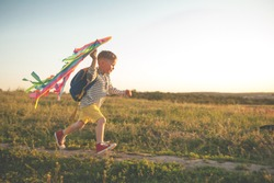 Happy child playing with a kite while running on meadow, sunset. Funny time with family. Little boy launch a kite. Travel and vacation in summer. Freedom