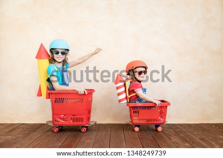 Happy child playing with toy rocket at home. Funny kid driving toy car indoor. Success and win concept