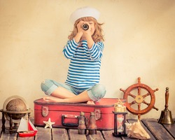 Happy child playing with vintage nautical things. Kid having fun at home. Summer sea dream and imagination. Adventure and travel concept. Retro toned image