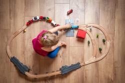 Happy child playing with wooden toy, build toy railroad at home or daycare. Top view of cute little girl playing with toy train. Educational toys for preschool and kindergarten child.