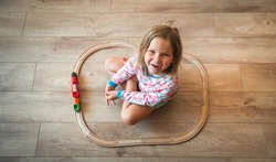 Happy child playing with wooden toy, Top view of cute little girl playing with toy train. Educational toys for preschool and kindergarten child.