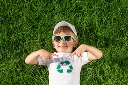 Happy child points fingers at recycle sign on t-shirt. Funny kid against spring green background. Ecology and Earth day concept. Top view