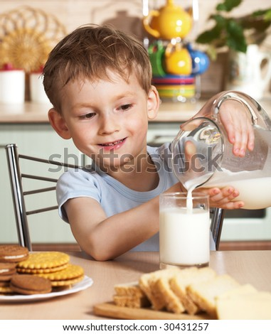 Happy child pours milk from jug