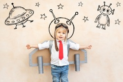 Happy child pretend to be astronaut. Funny kid playing at home. Dream and imagination concept