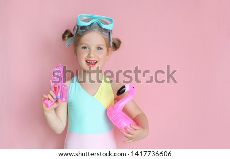 Happy child ready for a summer vacation. Kid having fun. Girl wearing swimsiut and swimming mask , holding water gun and inflatable flamingo . Summer holidays and vacation concept. Copyspace for text.