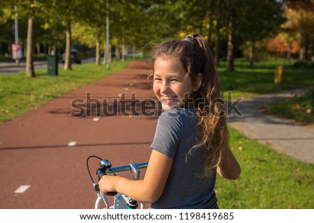 Happy child rides a bike on bike path. Cyclist child or teenager girl enjoys good weather and cycling. Environmentally friendly transport concept. Girl is smiling and laughs. Netherlands, Holland. stock photo