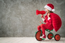 Happy child rides a retro bike. Kid playing at home. Christmas Xmas winter holiday concept