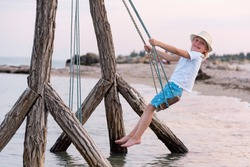 Happy child rides on rope swing over water. Swing by the sea. Holidays with children at sea