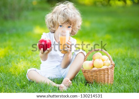 Happy child sitting on green grass and drinking apple juice in spring park. Healthy eating concept