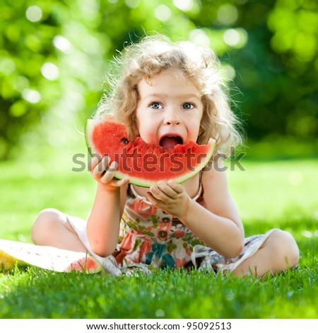 Happy child sitting on green grass and eating watermelon outdoors in spring park against natural sunny blurred background
