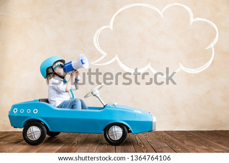 Happy child speaking to megaphone at home. Funny kid driving toy car indoor. Success and win concept