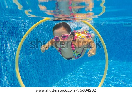 Happy child swims underwater in swimming pool. Smiling active girl in pool. Kids sport and fun