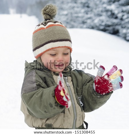 Happy child toddler, boy or girl, playing in fresh snow in winter.