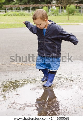 Happy child toddler playing in puddle after the rain.
