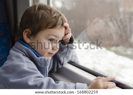Happy child traveling on train looking from the window.  - stock photo