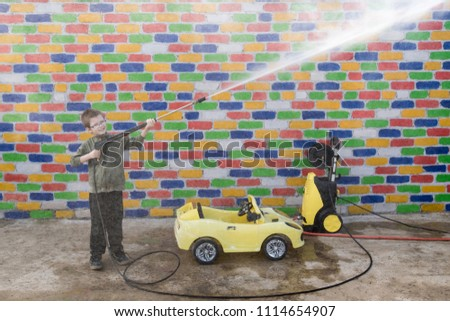 Happy child washes yellow toy car from high pressure washer in front of a multi-colored brick wall. Fun during the summer holidays. The concept of family business.