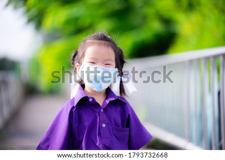 Happy child wear cloth mask when going to school. Asian girl smile sweet under face mask to prevent virus infection and to prevent dust and smoke when in public. Kid aged 3 year old life of New Normal Stock photo ©