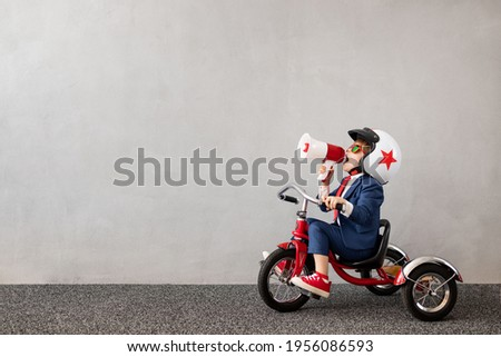 Happy child wearing suit riding bicycle against grey concrete wall background. Funny kid shouting through loudspeaker. Childhood dreams and business idea concept